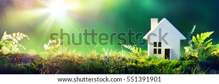 Eco Friendly House - Paper Home On Moss In Garden  Royalty-Free Stock Photo #551391901