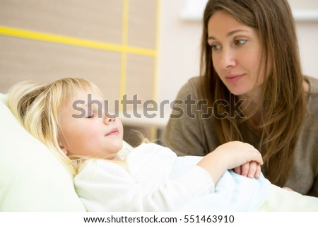 Sleeping well. Beautiful mature woman sitting near her daughterâ??s bed in the hospital ward looking at her sleeping child with love copyspace motherhood children health sleeping illness concept #551463910
