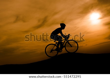 Silhouette of the cyclist riding a road bike at sunset.Mountain bicycle and man.Life style outdoor #551472295
