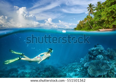 Woman swims around a coral reef surrounded by a multitude of fish. #551501362