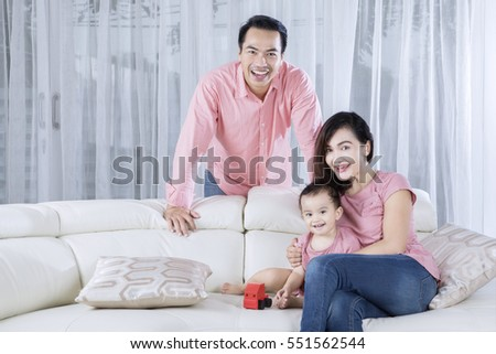 Image of happy family looking at the camera while sitting on the couch  #551562544