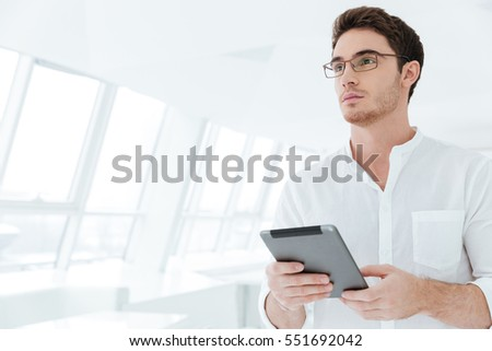 Image of attractive young man dressed in white shirt standing near big white window while holding tablet computer. Look aside. #551692042