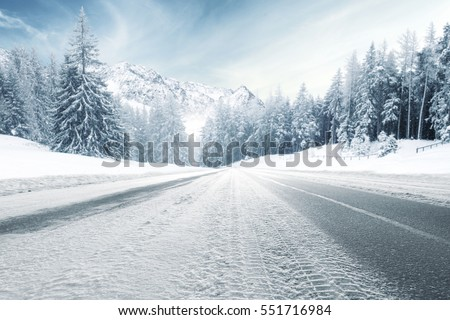 winter road and trees with snow and alps landscape  Royalty-Free Stock Photo #551716984
