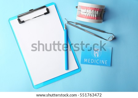 Business card, clipboard and dental tools on blue background. Medical service concept