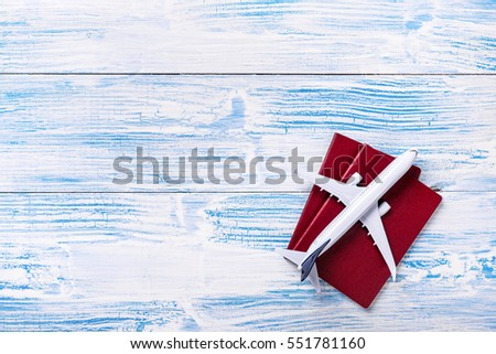 White blank model of passenger plane and passport on blue rustic wooden background  #551781160