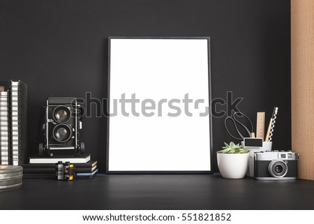Mock up photo frame with camera. White blank frame and medium format camera on photographer table.