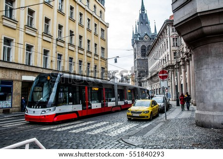 Tram on the streets of Prague / Modern articulated tram and car at the city street. #551840293
