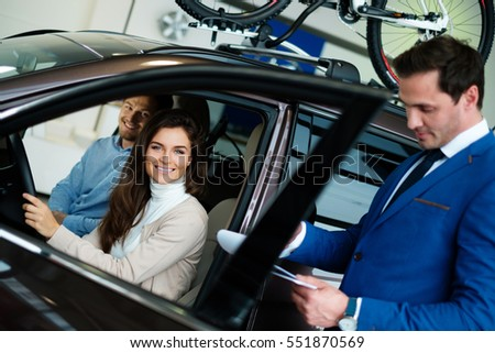 Beautiful young woman buys a car in the dealership saloon. #551870569