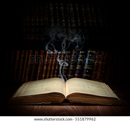 Open old book and ghost on a bookshelf background. Selective focus