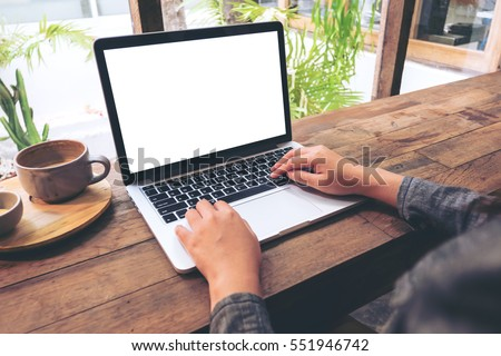 Mockup image of hands using laptop with blank white screen on vintage wooden table in cafe #551946742