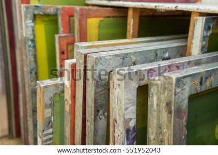 Silk screen printing screens stored in a wooden rack ready for printing. #551952043