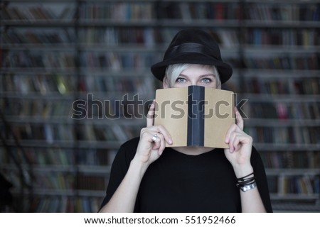 Portrait of woman in black hat with opened book, face half-covered, white hair. Hipster student girl in a library #551952466