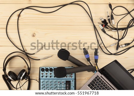Two microphones, headphones with a laptop, audio mixer with connection cables on a wooden table. View from above