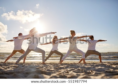 fitness, sport, yoga and healthy lifestyle concept - group of people making warrior pose on beach #551987794