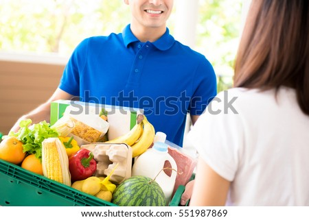 Delivery man delivering food to a woman at home - online grocery shopping service concept #551987869