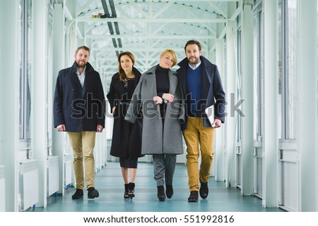 Two elegant couple dressed in coat going along the hall #551992816