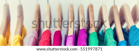 Banner horizontal crop for text background of clothing rack. Clothes for women hanging on hangers in home closet or shopping mall for store sale concept. Colorful selection of t-shirts. #551997871