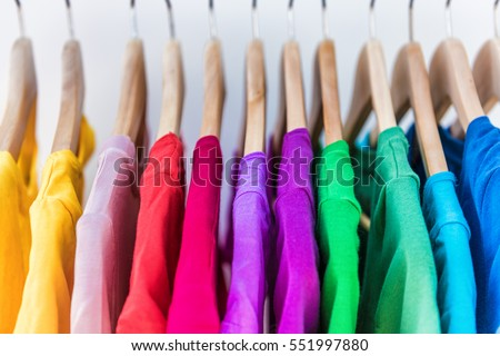 Fashion clothes on clothing rack - bright colorful closet. Closeup of rainbow color choice of trendy female wear on hangers in store closet or spring cleaning concept. Summer home wardrobe. #551997880
