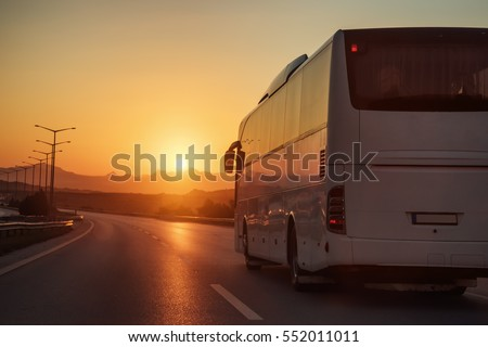 White bus driving on road towards the setting sun #552011011