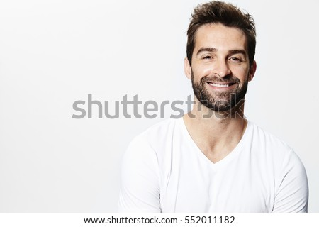 Smiling man in white t-shirt, portrait Royalty-Free Stock Photo #552011182
