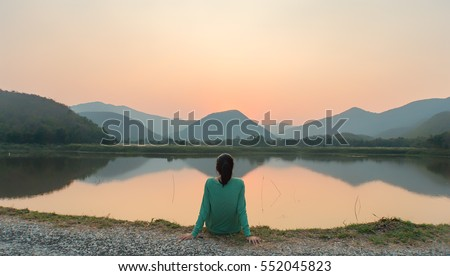 A woman is sitting at ease by the lake during sunset moment. #552045823