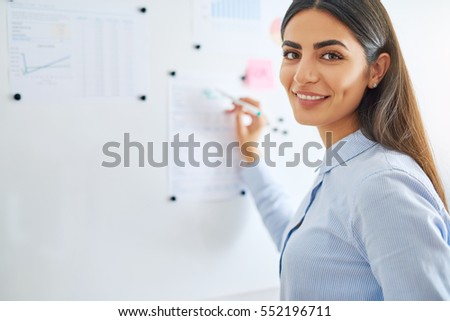 Happy young female business woman or teacher writing on white board with erasable marker Royalty-Free Stock Photo #552196711