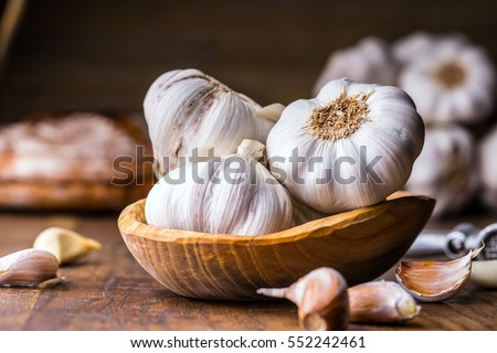 Garlic Cloves and Bulb in vintage wooden bowl. Royalty-Free Stock Photo #552242461