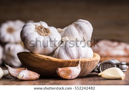 Garlic Cloves and Bulb in vintage wooden bowl. Royalty-Free Stock Photo #552242482