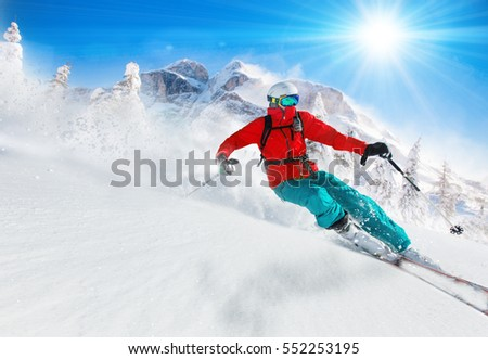 Skier skiing downhill during sunny day in high mountains #552253195