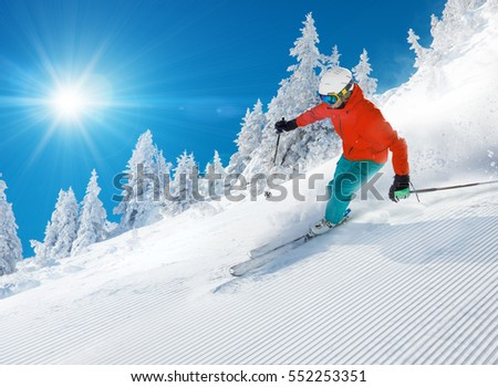 Skier skiing downhill during sunny day in high mountains #552253351