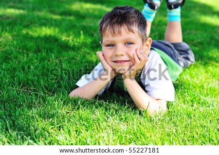 little boy laying on the sunny meadow #55227181