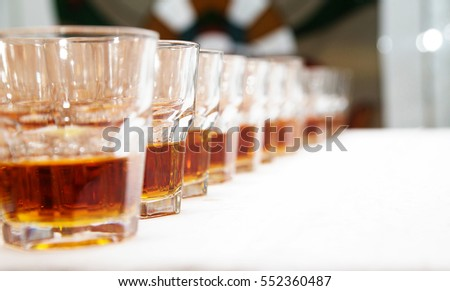 photo of Glasses with whiskey on white table #552360487