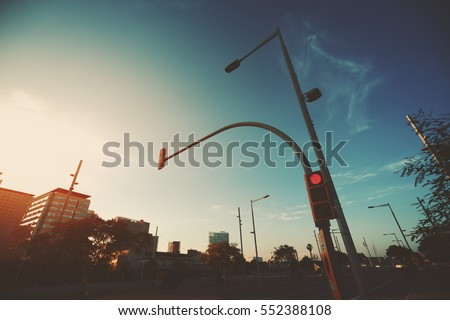 Wide angle shot of red traffic light on street lantern near highway, sunset and evening in residential Forum district of Barcelona, Spain, clear sky and distant spindrift clouds #552388108