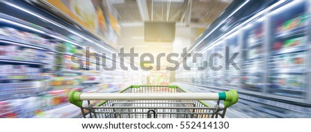 Panorama. Supermarket aisle with empty green shopping cart Royalty-Free Stock Photo #552414130
