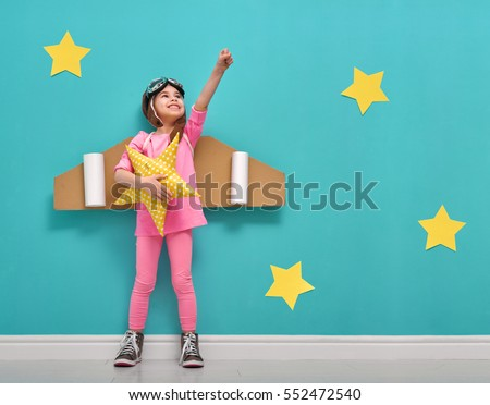 Little child girl in an astronaut costume is playing and dreaming of becoming a spaceman. Portrait of funny kid on a background of bright blue wall with yellow stars. #552472540