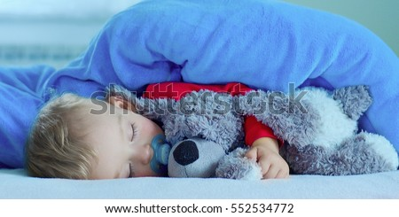 Cute toddler is sweetly sleeping with her dog under a blue blanket. #552534772
