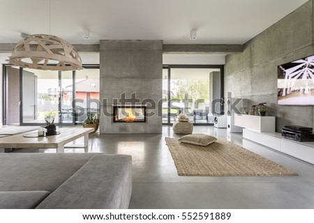 Spacious villa interior with cement wall effect, fireplace and tv Royalty-Free Stock Photo #552591889