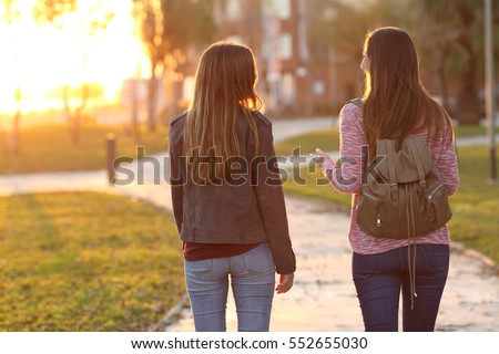 Back view of two friends walking together in a park at sunrise with a warm light in the background #552655030