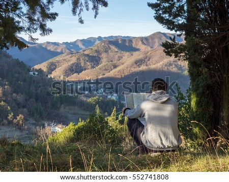 Man tourist in mountain read the map sitting on grass. Man on top of mountain under a tree shadow. Tourism concept #552741808