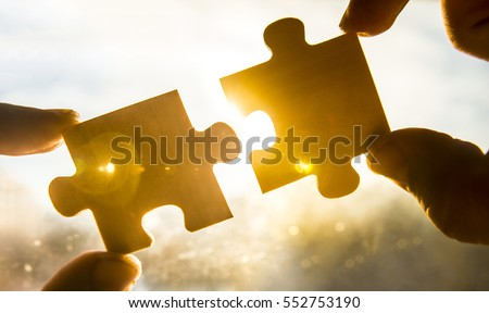 two hands trying to connect couple puzzle piece with sunset background. Jigsaw alone wooden puzzle against sun rays. one part of whole. symbol of association and connection. business strategy.  Royalty-Free Stock Photo #552753190