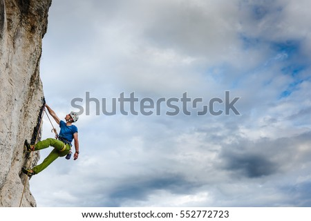 Young male climber hanging by a cliff #552772723