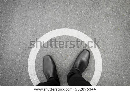 Businessman standing in white circle line feeling it is a limit and safety and never think different. Royalty-Free Stock Photo #552896344