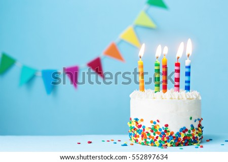 Birthday cake with colorful candles Royalty-Free Stock Photo #552897634