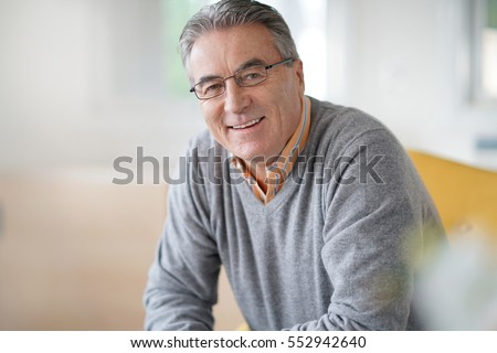 Smiling senior man with eyeglasses relaxing in armchair #552942640