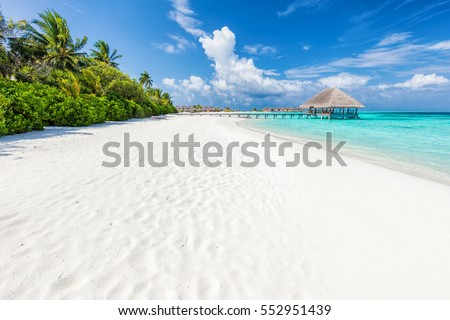 Wide sandy beach on a tropical island in Maldives. Coconut palms and water lodge on Indian Ocean. Royalty-Free Stock Photo #552951439