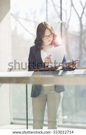 Businesswoman reviewing documents against railing in office #553012714