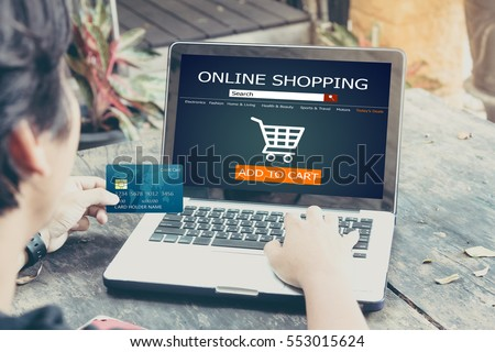Online shopping concept.man using laptop and holding credit card,color filter #553015624