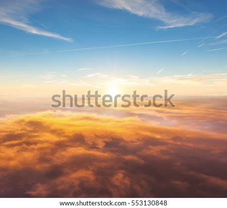 Beautiful sunset above clouds from airplane perspective. High resolution image #553130848