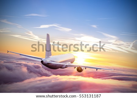 Commercial airplane flying above clouds in dramatic sunset light. Very high resolution of image #553131187