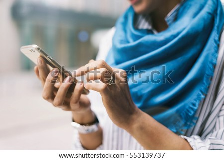 Close up photo of young girl reading messages on a smartphone while standing on urban background. Electronic device in the hands of hipster girl who is posting tweets  by using mobile application. #553139737